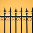 Old fashioned spike fence against yellow wall, some snow — Stock Photo #9283530