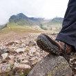 Stock Photo: Tourist in hiking shoes standing atop mountain