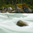 Stone in the river, long exposure-water motion blurred — Foto Stock