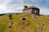 Fresh grave by stone church in the country — Stock Photo