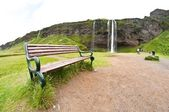 Bench for resting near the waterfall — Stock Photo