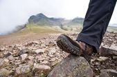 Tourist in hiking shoes standing atop the mountain — Stock Photo