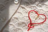 Needle with red thread in the shape of a heart — Stock Photo