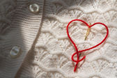 Needle with red thread stuck to the heart — Stock Photo