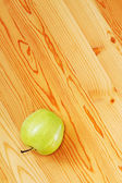 Green apple on a wooden surface — Stock Photo
