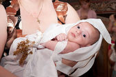 Baby baptized in the arms of his godmother — Stock Photo