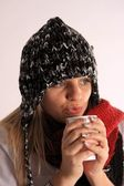 Woman with a warm hood with hot tea — Стоковое фото