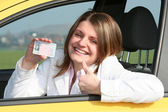 Young woman showing her driver license — Stock Photo
