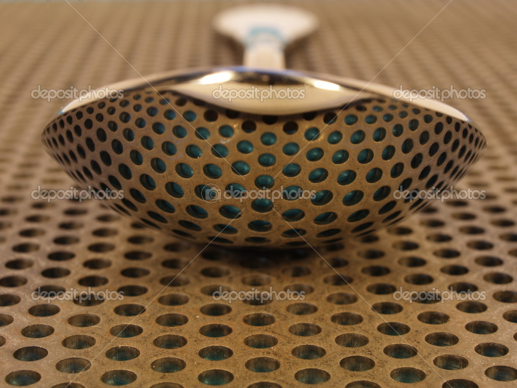 Spoon on perforated steel plate, reflecting the holes — Stock Photo #8847450