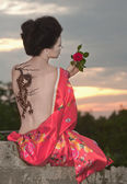 Geisha with dragon tattoo at sunset — Stock Photo
