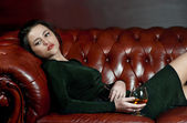 Young woman with a glass of brandy — Stock Photo