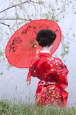 Geisha with red umbrella at the riverside — Stock Photo