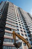 Yellow excavator on the constructions area — Stock Photo