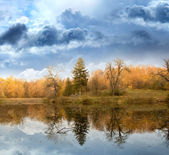 Autumn landscape against the terrible sky and the river — Stock Photo