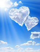 Hearts in clouds against a blue clean sky — Stock fotografie
