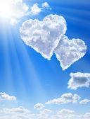 Srdce v oblacích proti modré obloze čisté — Stock fotografie