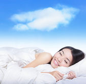 Young girl sleeping on a pillow with white cloud — Stock Photo