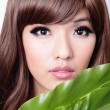 Woman face and green leaf — Stock Photo