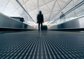 Passenger (Man) rushing through an escalator in airport terminal — Stok fotoğraf