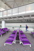Row of purple chair at airport with moving traveler — Stock Photo