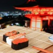 Foto Stock: Delicious Japanese sushi mix with beautiful japan night scenes