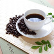 Coffee bean and hot coffee with green leaf - Stock Photo