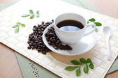 Coffee bean and hot coffee with green leaf — Stock Photo