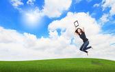 Mutlu kız atlamak ve dokunmatik yüzey bilgisayar çayır üzerinde göster — Stok fotoğraf