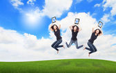 Happy Girl Jump and show touch pad computer on the meadow — Stock Photo