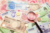 Asian currency, magnifying glass and Background of asian currency — 图库照片