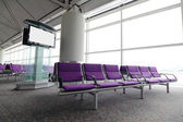LCD TV and row of purple chair at airport — Stockfoto