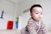 Närbild av allvarliga baby ansikte med hem backgroung — Stockfoto