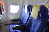 Airplane blue seat and window inside an aircraft — Stock Photo