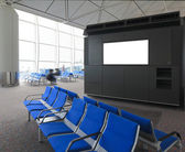 Blank billboard and blue chair in international airport — Stock Photo
