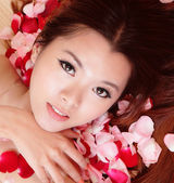 Beauty Girl smiling close-up with rose background — Stock Photo