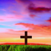 Cross silhouette on grass with sunset background — Stock Photo