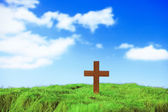 Wood cross on green grass — Stock Photo
