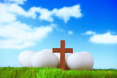 White eggs and wood cross on grass with blue sky — Stock Photo