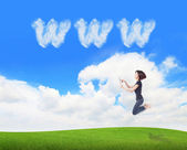 Girl jump and using tablet pc with www cloud — Stock Photo