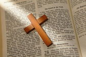 Wooden cross on a old bible — Stock Photo