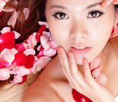 Girl smiling and touch face with red rose — Stock Photo