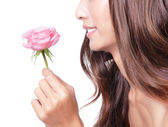 Young pretty woman enjoying smell pink rose — Stock Photo