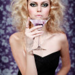 Beautiful blond young female with purple cocktail on a floral background — Stock Photo #8531968