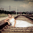 Beautiful thoughtful brunette bride is sitting on the railway and waiting - Stock Photo