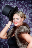 Smiling beautiful woman in fur is holding black hat — Stock Photo