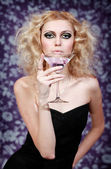 Beautiful blond young female with purple cocktail on a floral background — Stock Photo