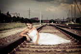 Beautiful thoughtful brunette bride is sitting on the railway and waiting — Stock Photo