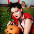 Stock Photo: Beautiful gothic female holding halloween pumpkin