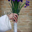 Stock Photo: Bride is holding her wedding iris bouquet on a old castle wall background
