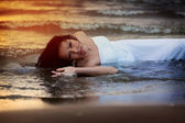 Attractive young woman in wedding dress enjoys sea water during the sunset — Stock Photo